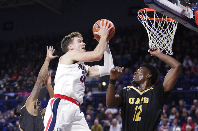 Gonzaga forward Corey Kispert, center, shoots between Arkansas-Pine Bluff guard Zavian Jackson, left, and forward Terrance Banyard during the first half of an NCAA college basketball game in Spokane, Wash., Saturday, Nov. 9, 2019. (AP Photo/Young Kwak)