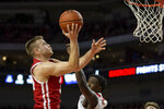 Wisconsin guard Brad Davison (34) makes a lay up against Nebraska forward Kevin Cross (1) during the first half of an NCAA college basketball game in Lincoln, Neb., Saturday, Feb. 15, 2020. (AP Photo/John Peterson)