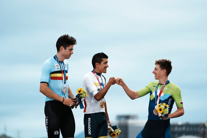 Richard Carapaz of Ecuador, center, who won the gold medal, fist pumps bronze medal winner Tadej Pogacar of Slovenia, as silver medal winner Wout van Aert of Belgium watches, after the men's cycling road race at the 2020 Summer Olympics, Saturday, July 24, 2021, in Oyama, Japan. (AP Photo/Thibault Camus)