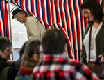 Johnson Roberts, of Chesterfield, N.H., exits the voting booth while Allison Watt signs in with officials to cast her ballot during the New Hampshire presidential primary elections in Chesterfield, N.H., Tuesday, Feb. 11, 2020. (Kristopher Radder/The Brattleboro Reformer via AP)