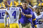 LSU coach Ed Orgeron congratulates running back John Emery Jr. (4), who scored against Arkansas during the second half of an NCAA college football game in Baton Rouge, La., Saturday, Nov. 23, 2019. (AP Photo/Matthew Hinton)