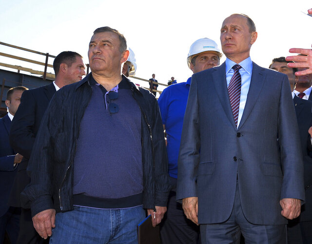 FILE - In this Sept. 15, 2016, file photo, Russian President Vladimir Putin, right, joins businessman and billionaire Arkady Rotenberg, during to a visit to the construction site of the Kerch Strait bridge in Kerch, Crimea. Investigators traced $18 million in art buys to shell companies linked to Arkady Rotenberg and his brother Boris, who are close Putin associates who American officials say benefited financially from the Crimean annexation. (Alexei Druzhinin/Sputnik, Kremlin, File Pool Photo via AP)