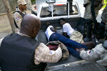 In this Sunday, Nov. 10, 2019 photo, police officers detain two men whom they claim stole an inverter battery during a protest to demand the resignation of President Jovenel Moise, in Port-au-Prince, Haiti. Anger over corruption, inflation and scarcity of basic goods, including fuel, has led to more than a month of demonstrations that have paralyzed the country as protesters demand the resignation of President Moise. (AP Photo/Dieu Nalio Chery)