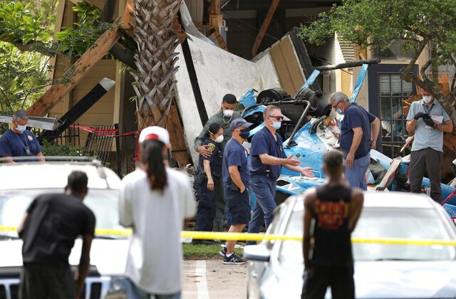Authorities investigate the scene of a helicopter crash at an apartment complex in Houston,  Saturday, May 2, 2020.  Houston Police Chief Art Acevedo says the helicopter was carrying a pilot and a tactical flight officer when it went down at an apartment complex in north Houston around 2 a.m. Saturday.  The cause of the crash wasn't immediately known. (Jon Shapley/Houston Chronicle via AP)/Houston Chronicle via AP)