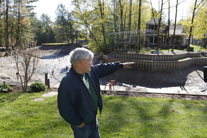 Home owner Glenn Hart describes where the water level was next to Wixom Lake, in Edenville Township, Mich., Thursday, May 21, 2020, before the Edenville Dam failed and flood waters rushed south. (AP Photo/Carlos Osorio)