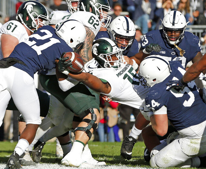 Michigan State's La'Darius Jefferson (15) punches it in for a touchdown against Penn State during the first half of an NCAA college football game in State College, Pa., Saturday, Oct. 13, 2018. (AP Photo/Chris Knight)