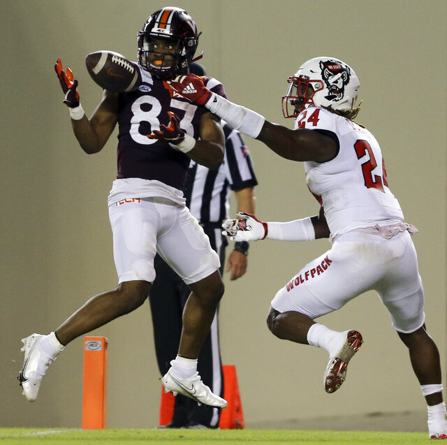 Virginia Tech's Tayvion Robinson, left, catches a touchdown pass in front of North Carolina State's Malik Dunlap, right, during the second quarter of an NCAA college football game Saturday, Sept. 26, 2020, in Blacksburg, Va. (Matt Gentry/The Roanoke Times via AP, Pool)