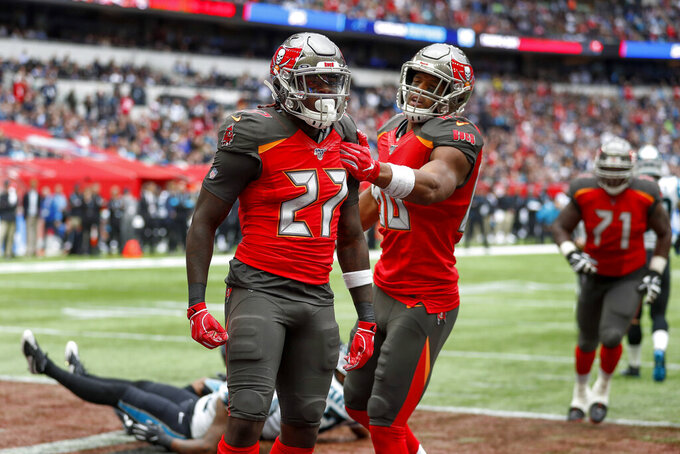 Tampa Bay Buccaneers running back Ronald Jones (27) celebrates with teammates after scoring a touchdown against the Carolina Panthers during the second quarter of an NFL football game, Sunday, Oct. 13, 2019, at Tottenham Hotspur Stadium in London. (AP Photo/Alastair Grant)