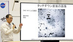 Associate Prof. Yuichi Tsuda of the Japan Aerospace Exploration Agency (JAXA) speaks about the touchdown by the Hayabusa2 spacecraft near an image of the surface of the asteroid Ryugu during a press conference in Sagamihara, near Tokyo, Friday, Feb. 22, 2019. Hayabusa2 touched down on the distant asteroid Friday on a mission to collect material that could provide clues to the origin of the solar system and life on Earth. (Kyodo News via AP)