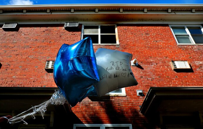 Balloons are left to remember a baby boy killed and two girls critically injured in a Sunday fire in the Clinton-Peabody public housing complex in St. Louis on Monday, Oct. 21, 2019. At least a few small children died after they were left alone in a St. Louis apartment that caught fire and a woman is in custody while the blaze is investigated, authorities said. (Robert Cohen/St. Louis Post-Dispatch via AP)
