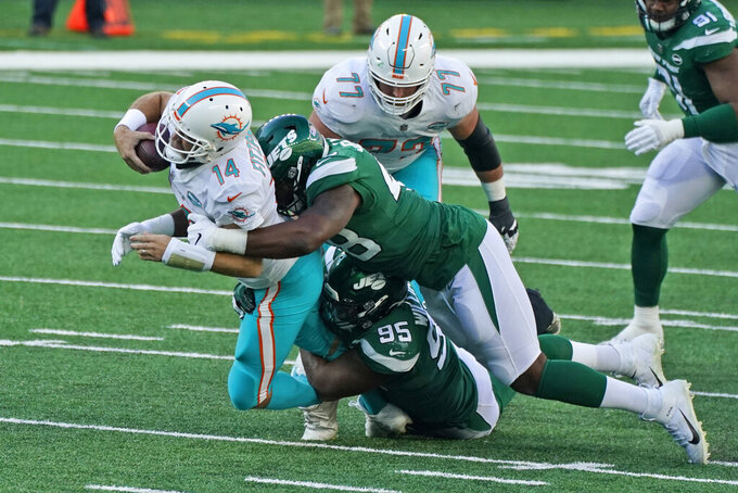 New York Jets defense tackles Miami Dolphins quarterback Ryan Fitzpatrick, left, during the first half of an NFL football game, Sunday, Nov. 29, 2020, in East Rutherford, N.J. (AP Photo/Corey Sipkin)