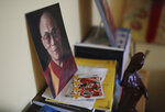 A photo of the Dalai Lama sits next to a football trading card on a bookshelf in Jalue Dorje's bedroom in Columbia Heights, Minn., on Monday, July 19, 2021. When he was an infant, Jalue, now 14, was identified as the eighth reincarnation of the lama Terchen Taksham Rinpoche. After finishing high school in 2025, Jalue will head to northern India and join the Mindrolling Monastery, more than 7,200 miles (11,500 kilometers) from his home. (AP Photo/Jessie Wardarski)