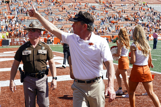 Oklahoma State head coach Mike Gundy gives a thumbs up to fans after their 32-24 win over Texas in an NCAA college football game in Austin, Texas, Saturday, Oct. 16, 2021. (AP Photo/Chuck Burton)