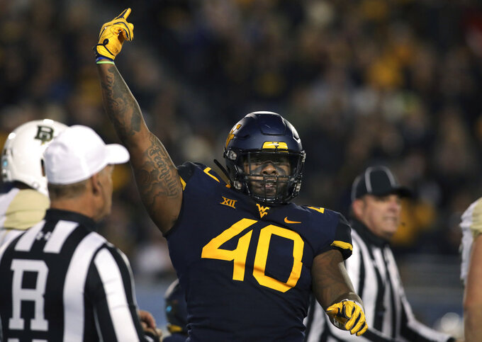 West Virginia defensive lineman Kenny Bigelow Jr. (40) celebrates making a tackle during the first half of an NCAA college football game against Baylor, Thursday, Oct. 25, 2018, in Morgantown, W.Va. (AP Photo/Raymond Thompson)