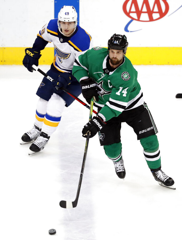 Dallas Stars left wing Jamie Benn (14) controls the puck in front of St. Louis Blues left wing Ivan Barbashev (49) during the first period of an NHL hockey game in Dallas, Thursday, Feb. 21, 2019. (AP Photo/Tony Gutierrez)