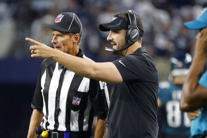 Philadelphia Eagles head coach Nick Sirianni, front, talks with an official in the first half of an NFL football game against the Dallas Cowboys in Arlington, Texas, Monday, Sept. 27, 2021. (AP Photo/Michael Ainsworth)
