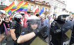 In this Aug. 10, 2019, photo, police hold back protesters protecting a gay pride parade in Plock, Poland. Activists say months of anti-gay rhetoric by politicians and church leaders in the lead-up to parliamentary elections have created an atmosphere that's increasingly hostile to the LGBT community. (AP Photo/Czarek Sokolowski)