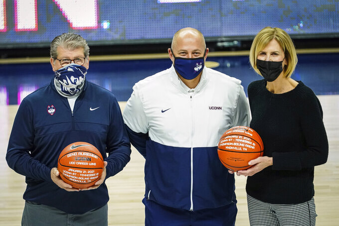 Connecticut director of athletics David Benedict presents a special game balls to head coach Geno Auriemma, left, and associate head coach Chris Dailey before an NCAA college basketball game against Marquette, Monday, March 1, 2021, in Storrs, Conn. (David Butler II/Pool Photo via AP)