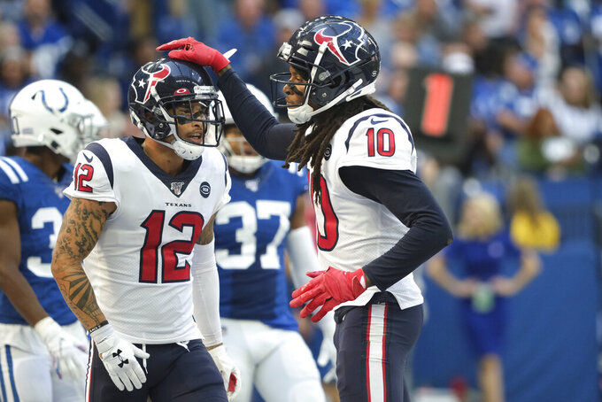 Houston Texans' DeAndre Hopkins (10) celebrates  with Kenny Stills (12) after scoring a touchdown during the second half of an NFL football game against the Indianapolis Colts, Sunday, Oct. 20, 2019, in Indianapolis. (AP Photo/AJ Mast)