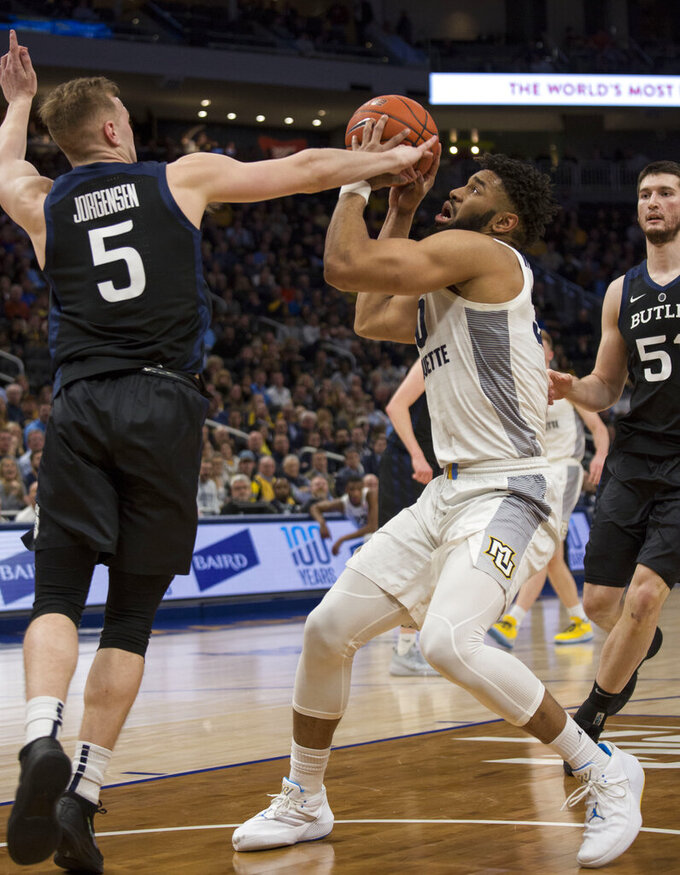 Marquette's Ed Marrow, right, is defended by Butler's Paul Jorgensen, left, during the first half of an NCAA college basketball game Wednesday, Feb. 20, 2019, in Milwaukee. (AP Photo/Darren Hauck)