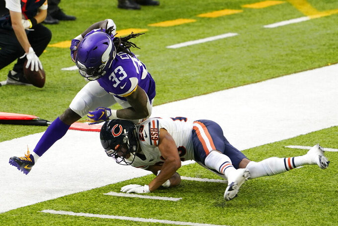 Minnesota Vikings running back Dalvin Cook (33) is tackled by Chicago Bears cornerback Kyle Fuller during the second half of an NFL football game, Sunday, Dec. 20, 2020, in Minneapolis. (AP Photo/Jim Mone)