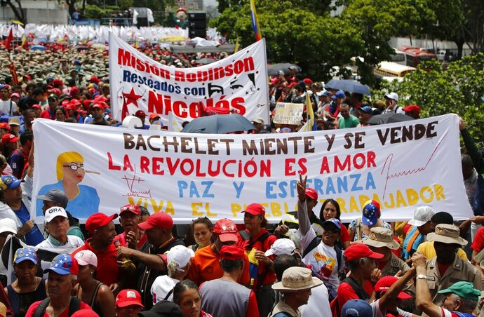 Supporters of President Nicolas Maduro holds up a banner with a message that reads in Spanish: