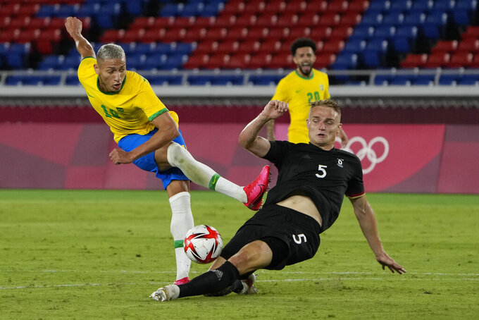 Germany's Amos Pieper blocks Brazil's Richarlison during a men's soccer match at the 2020 Summer Olympics, Thursday, July 22, 2021, in Yokohama, Japan. (AP Photo/Kiichiro Sato)