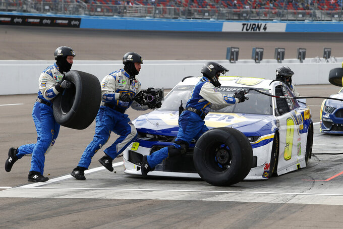 The pit crew for Chase Elliott scramble around the car on a tire change pit stop during the NASCAR Cup Series auto race at Phoenix Raceway, Sunday, Nov. 8, 2020, in Avondale, Ariz. (AP Photo/Ralph Freso)