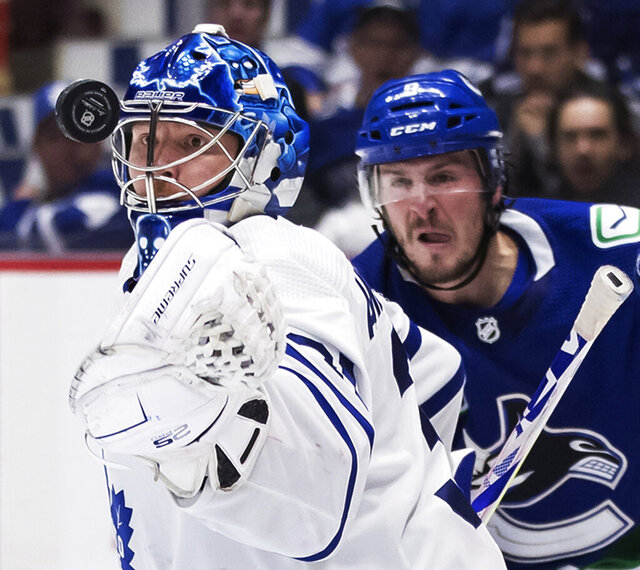 Toronto Maple Leafs goalie Frederik Andersen, of Denmark, watches the puck after stopping Vancouver Canucks' J.T. Miller, back right, during the second period of an NHL hockey game against the Toronto Maple Leafs, in Vancouver, British Columbia, on Tuesday, Dec. 10, 2019. (Darryl Dyck/The Canadian Press via AP)