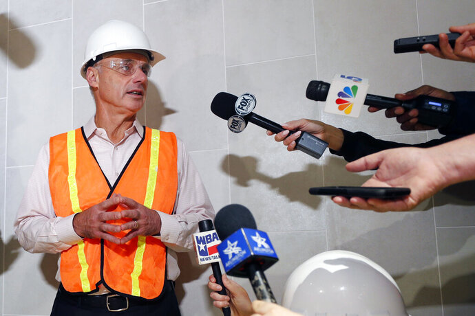 Baseball Commissioner Rob Manfred speaks to the media during a tour of the under construction new Texas Rangers stadium in Arlington, Texas, Tuesday, Nov. 19, 2019. Manfred hopes the investigation into sign stealing by the Houston Astros will be completed by next season and says he has broad authority to impose discipline beyond fines, the loss of amateur draft picks and taking away international signing bonus pool allocation. (AP Photo/LM Otero)