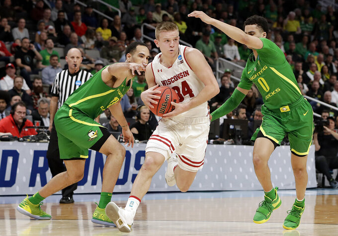 Wisconsin guard Brad Davison (34) drives between Oregon forward Paul White, left, and guard Will Richardson (0) during the second half of a first round men's college basketball game in the NCAA Tournament, Friday, March 22, 2019, in San Jose, Calif. (AP Photo/Chris Carlson)