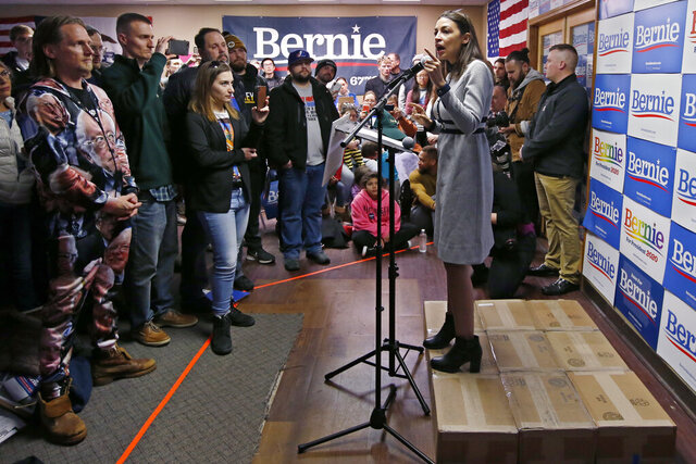 Standing on a makeshift stage made of cardboard boxes, Rep. Alexandria Ocasio-Cortez, D-N.Y., speaks as a surrogate of Democratic presidential candidate Bernie Sanders at a canvass launch Saturday, Jan. 25, 2020, in Cedar Rapids, Iowa. (AP Photo/Sue Ogrocki)