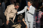 Brazil's President Jair Bolsonaro takes a bow next to televangelist R.R. Soares, at an International Grace of God Church event, at Botafogo beach in Rio de Janeiro, Brazil, Saturday, Feb. 15, 2020. Tens of thousands of people gathered to celebrated the 40th anniversary of the evangelical church. (AP Photo/Leo Correa)