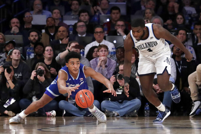Seton Hall guard Jared Rhoden (14) and Villanova forward Eric Paschall (4) compete for the ball during the second half of an NCAA college basketball game in the championship of the Big East Conference tournament, Saturday, March 16, 2019, in New York. Villanova won 74-72. (AP Photo/Julio Cortez)