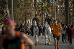 Mounted police patrol on horses as people exercise on a seafront promenade in Barcelona, Spain, Sunday, May 3, 2020. Spaniards have filled the streets of the country to do exercise after seven weeks of confinement to their homes to fight the coronavirus pandemic. People ran, walked, or rode bicycles under a brilliant sunny sky in Barcelona on Saturday, where many flocked to the maritime promenade to get as close as possible to the still off-limits beach. (AP Photo/Emilio Morenatti)