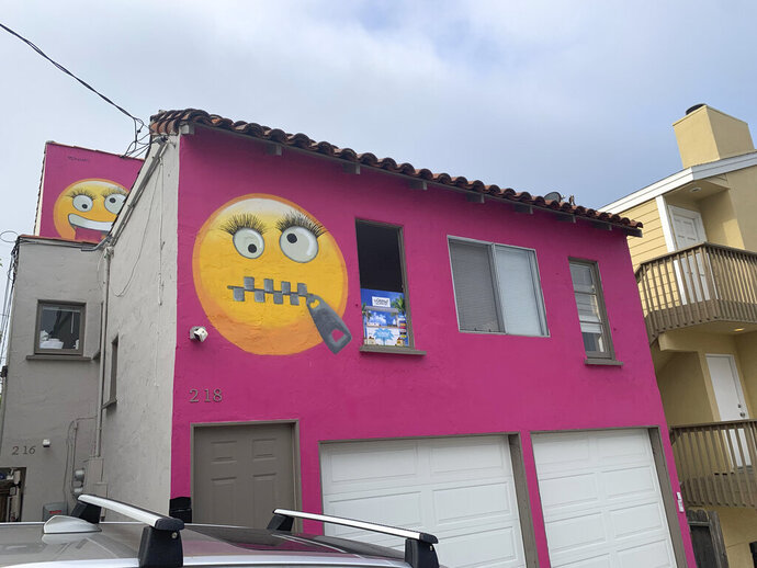 Painted emoji are seen on a house in Manhattan Beach, Calif. on Wednesday, Aug. 7, 2019. The Southern California seaside community is in an uproar after the home was given the new paint job featuring two huge emojis on a bright pink background. Manhattan Beach residents railed against the makeover during a City Council meeting Tuesday night, citing problems with spectators. (AP Photo/Natalie Rice)