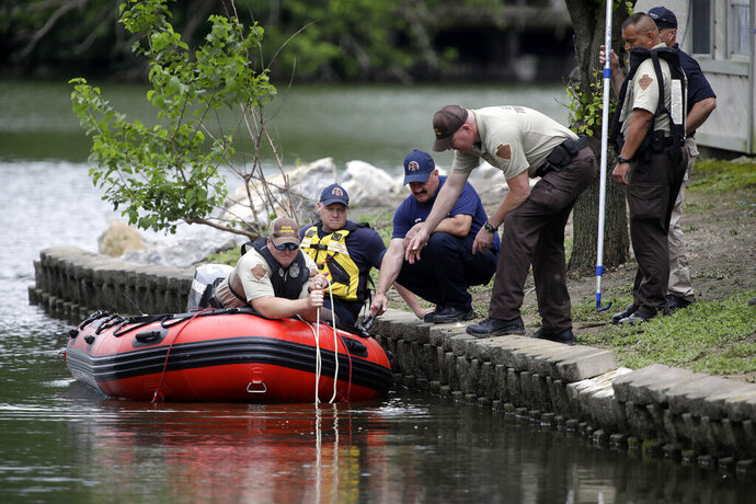 In this Tuesday, May 26, 2020, photo, emergency personnel dredge a pond at Shoreline Lakeside Apartments during their search for missing children Miracle Crook, 3, and Tony Crook, 2, in Tulsa, Okla. Searchers used sonar to examine the pond for the two young children last seen days ago with their noncustodial mother, who was arrested after being questioned about their disappearance. (Mike Simons/Tulsa World via AP)