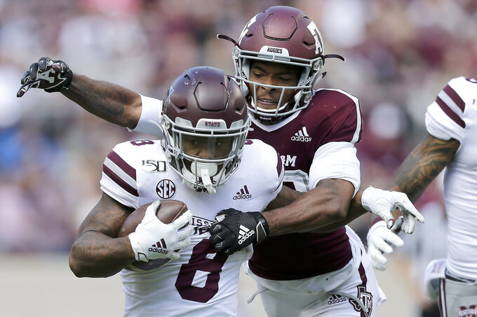 Mississippi State running back Kylin Hill (8) tries to fight off a tackle by Texas A&M defensive back Clifford Chattman (22) during the second half of an NCAA college football game, Saturday, Oct. 26, 2019, in College Station, Texas. (AP Photo/Sam Craft)