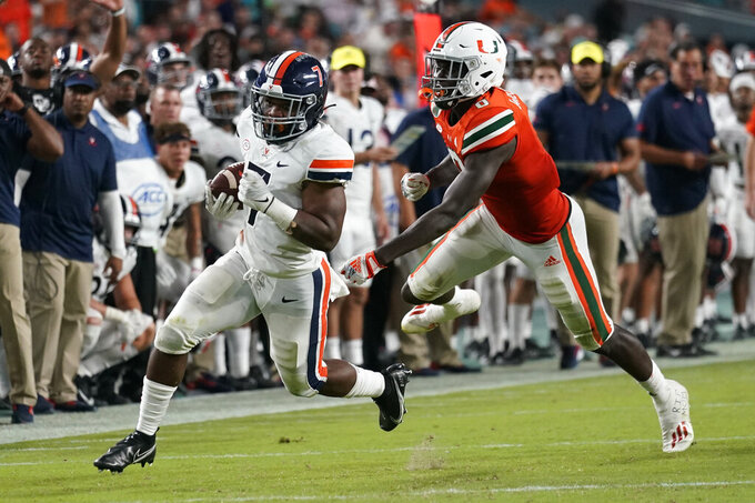 Virginia Cavaliers running back Mike Hollins (7) runs ahead of Miami Hurricanes safety James Williams for a touchdown during the first half of a NCAA college football game, Thursday, Sept. 30, 2021, in Miami Gardens, Fla. (AP Photo/Lynne Sladky)