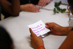 """In this Sept. 24, 2019, photo, a migrant girl in U.S. government custody holds a card that says, in Spanish, """"It doesn't matter where you come from, it matters where you are going,"""" during a lesson on reproductive health and self esteem in Lake Worth, Fla. Detention can be traumatic for children, and the nonprofit U.S. Committee for Refugees and Immigrants opened the federally funded Rinconcito del Sol shelter this summer, aiming to make it a model of excellence. Rinconcito del Sol is one of 170 detention centers, residential shelters and foster programs in 23 states which held nearly 70,000 migrant kids in the past year. (AP Photo/Wilfredo Lee)"""