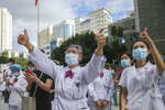 Medical workers give thumbs-up to their colleagues leaving to help with an outbreak of COVID-19 in Putian from a provincial hospital in Fuzhou in southeast China's Fujian province Sunday, Sept. 12, 2021. Putian, a city in southern China that is trying to contain a coronavirus outbreak told the public Sunday not to leave, suspended bus and train service and closed cinemas, bars and other facilities. (Chinatopix via AP)
