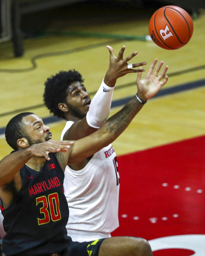 Maryland forward Galin Smith (30) and Rutgers center Myles Johnson (15) battle for the ball during the first half of an NCAA college basketball game in Piscataway, N.J., Sunday, Feb. 21, 2021. (Andrew Mills/NJ Advance Media via AP)