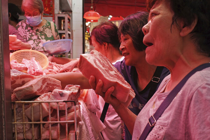 In this Thursday, May 16, 2019, photo, customers buy frozen pork at a local market in Hong Kong. A case of African swine fever has been detected in a Hong Kong slaughterhouse, prompting the culling of all 6,000 pigs at the facility. Secretary for Food and Health Sophia Chan said in a statement Friday that the incurable virus was found in a single pig imported from a farm in Guangdong province in mainland China, where the monthslong outbreak has devastated herds. (AP Photo/Kin Cheung)