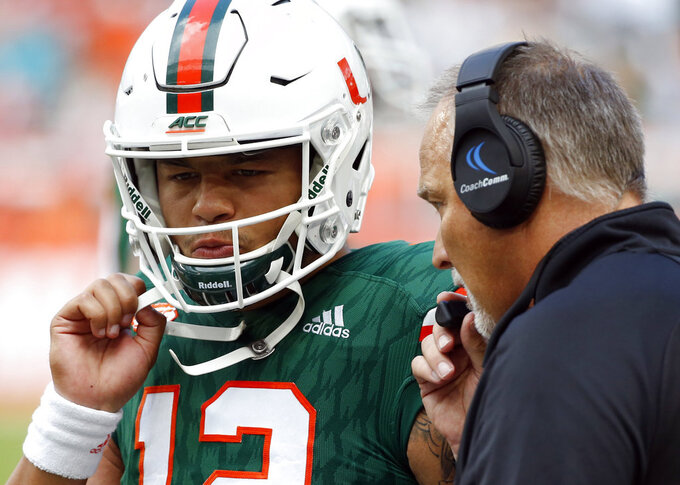 FILE - In this Oct. 14, 2017, file photo, Miami head coach Mark Richt talks with quarterback Malik Rosier (12) during the first half of an NCAA College football game against Georgia Tech in Miami Gardens, Fla. Miami has changed starting quarterbacks again, with Rosier returning to the first-string spot that he lost to N'Kosi Perry three games ago. (AP Photo/Wilfredo Lee, File)