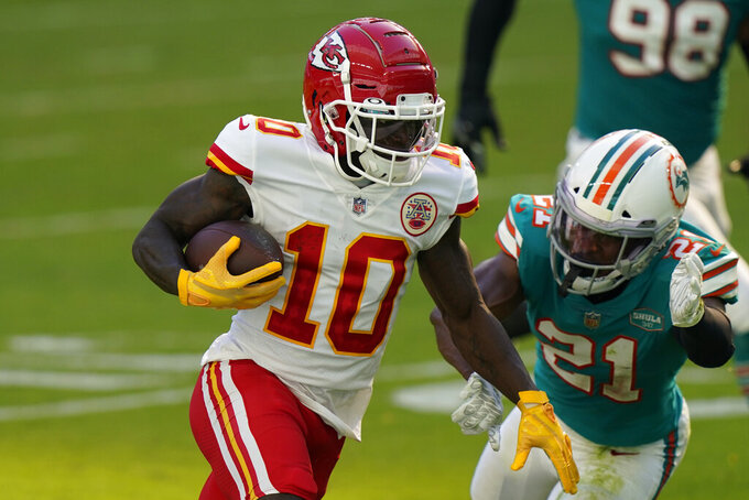 Kansas City Chiefs wide receiver Tyreek Hill (10) runs for a touchdown as Miami Dolphins free safety Eric Rowe (21) attempt to tackle, during the first half of an NFL football game, Sunday, Dec. 13, 2020, in Miami Gardens, Fla. (AP Photo/Lynne Sladky)