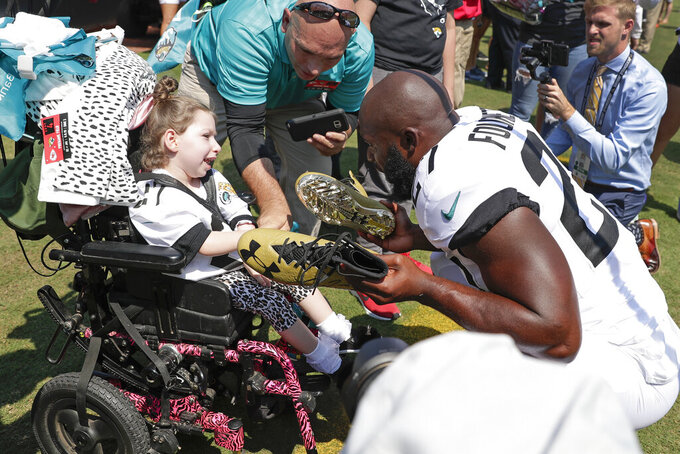 Jacksonville Jaguars running back Leonard Fournette, front right, presents a pair of autographed cleats to Arianna Hopper, of Brunswick, Ga., before an NFL football game against the Kansas City Chiefs, Sunday, Sept. 8, 2019, in Jacksonville, Fla. (AP Photo/John Raoux)