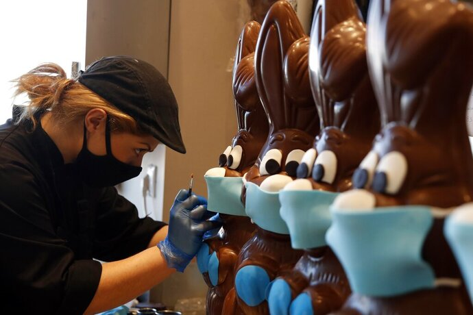 An employee of cake shop prepares chocolate Easter bunnies with masks in Lykovrisi, northern Athens, on Wednesday, April 8, 2020. Cake shops and bakeries in Greece have remained open during a strict circulation ban in Greece to contain the spread of the COVID-19, but authorities have intensified a crackdown on lockdown violations ahead of Easter, which is celebrated by Orthodox Christians on April 19. Greece's Orthodox Church says it will not permit any public gatherings for Easter services. (AP Photo/Thanassis Stavrakis)