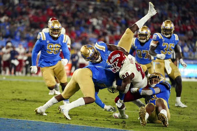 Fresno State running back Ronnie Rivers (20) is tackled by a group of UCLA defenders during the second half of an NCAA college football game Sunday, Sept. 19, 2021, in Pasadena, Calif. (AP Photo/Marcio Jose Sanchez)