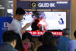 People watch a TV showing a file image of North Korea's missile launch during a news program at the Seoul Railway Station in Seoul, South Korea, Wednesday, Oct. 2, 2019. North Korea on Wednesday fired projectiles toward its eastern sea, South Korea's military said, in an apparent display of its expanding military capabilities ahead of planned nuclear negotiations with the United States this weekend. The sign reads: