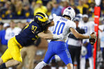 Michigan defensive lineman Aidan Hutchinson (97) tries to wrap up Middle Tennessee quarterback Asher O'Hara (10) during the second half of an NCAA college football game in Ann Arbor, Mich., Saturday, Aug. 31, 2019. (AP Photo/Paul Sancya)